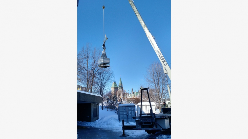 Using a crane to lift the sculpture over the terrace
