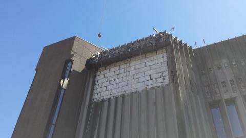 Des sections du revêtement extérieur en béton préfabriqué sont enlevées pour faire place à un nouvel ajout.