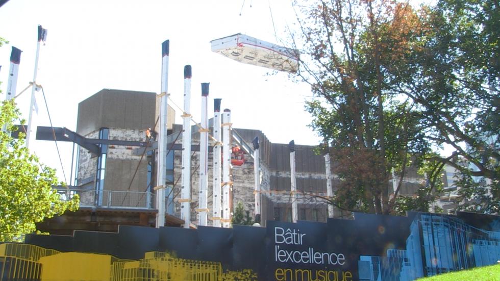 Une section de caissons de 60 pieds est soulevée par une grue au-dessus d'une nouvelle partie de l'immeuble.